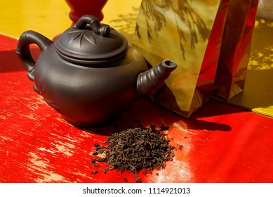 Black clay teapot with golden tea and coffee foil packaging bags. Loose leaf Chinese Puerh tea, that is produced in the Yunnan province. Reduces Blood Pressure, Balances Cholesterol, Fat Burning.