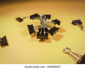 Black clips are arranged in various patterns on a colorful background.