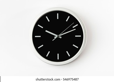 Black clock hanging at the wall