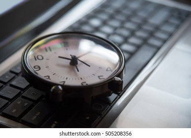 Black clock lay on keyboard time metaphor concept in dark low key tone, selective focus.