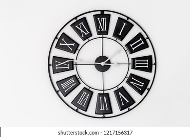 Black clock on a white wall