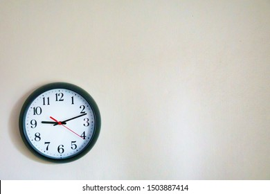Black clock showing 9.10 o'clock on the wall with Copy Space. Soft focus process.