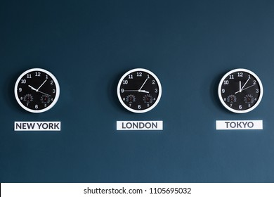 Black clocks on navy blue wall in businessman's home office interior