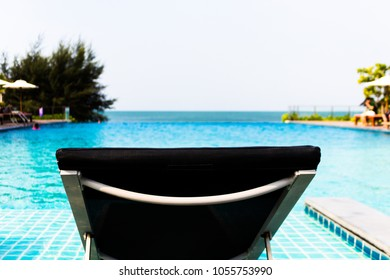 Black Cloth Of Beach Chair In Swimming Pool With Blue Ripped Water And  Background Sea Beach