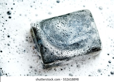 Black coal bar of soap in foam on dark background. Close-up composition.