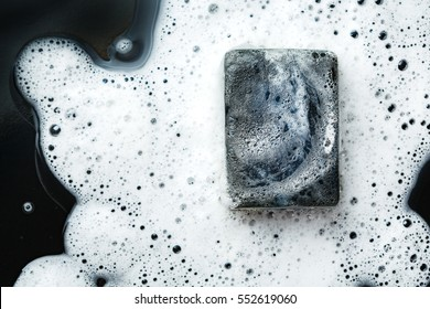 Black coal bar of soap in foam on dark background. Close-up composition. Top view.