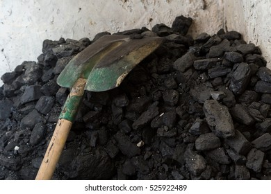 Black coal lying and shovel on a pile in house basement. Fuel material.