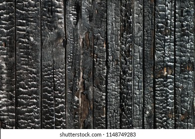 Black coal texture of the scorched wooden boards of the walls of the house. Ruined house building after a fire
