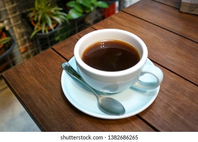 Black coffee, Americano in a cute blue color cup on wooden table