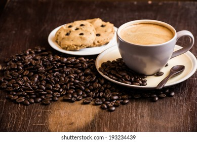 black coffee and coffee bean with cookie on wooden table
