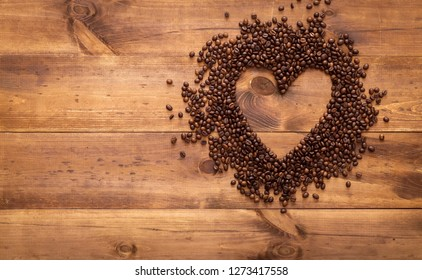 Black coffee beans seed in heart shape on brown wooden table, dark cofee arabica robusta roasted grain flavor aroma cafe, natural coffe shop background, top close up view from above, copy space