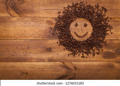 Black coffee beans seed in sun shape on brown wooden table as morning energy concept, dark cofee roasted grain flavor aroma cafe, natural coffe shop background, top view from above, copy space
