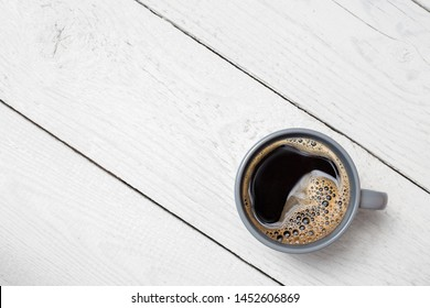 Black coffee in a blue-grey ceramic mug isolated on white painted wood from above. Space for text.
