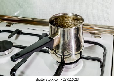 Black coffee is brewed and boils in a pot on the stove
