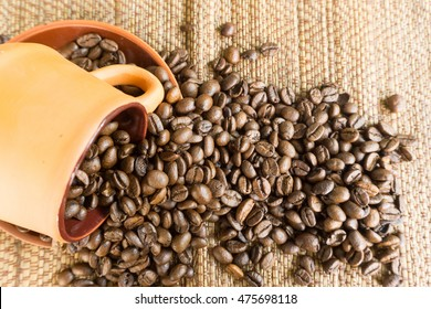 black coffee in brown cup pottery and roasted coffee beans on table