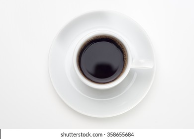 Black coffee with bubbles in white cup with coffee beans, view from above.