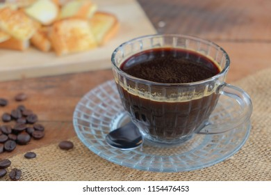 Black coffee and butter bread on wooden table