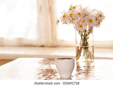 black coffee and chamomile in a vase on the table in front of the window in the morning