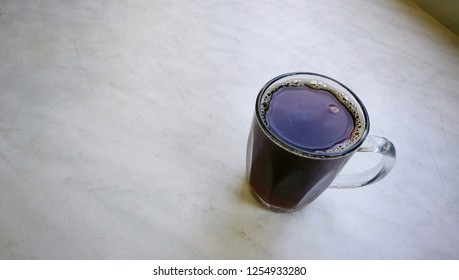 Black coffee in clear mug on top of white marble cafe table