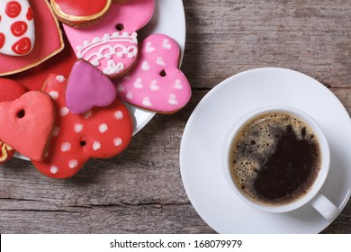 Black coffee and colorful heart cookies on a wooden table. top view. Valentine's day holiday