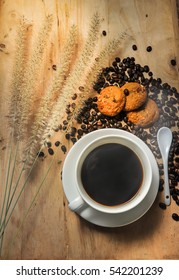 Black Coffee and cookie on a wood background.