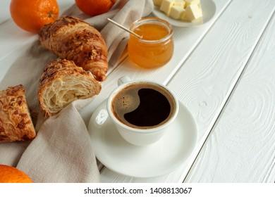 black coffee, croissants, orange jam on a light wooden table