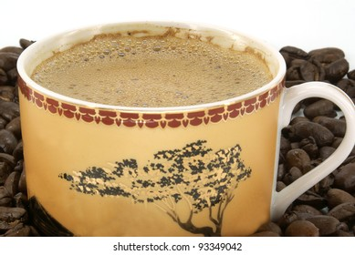 black coffee in cup against coffee beans