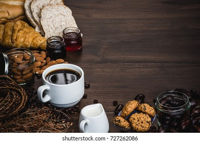 Black coffee  cup with bakery and coffee decoration. On black wood top table.