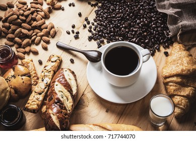 Black coffee  cup with bakery and coffee maker. On wood top table.