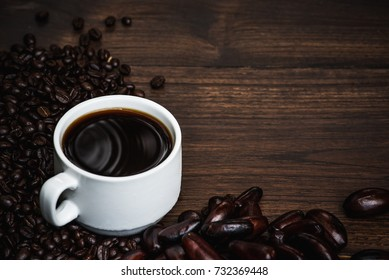 Black coffee  cup with coffee bean and black nut. On black wood top table.
