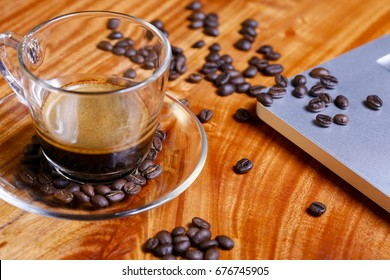 Black coffee cup and beans on table
