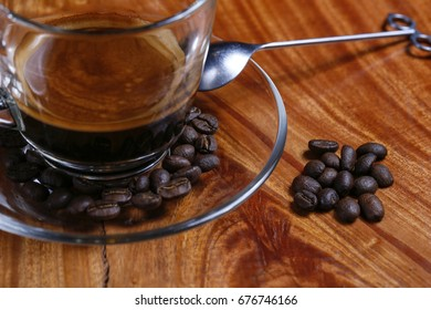 Black coffee cup, coffee beans and spoon on wooden table