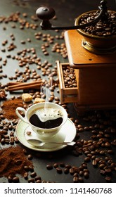 Black coffee in a cup on the background of coffee beans in a composition with accessories