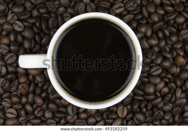 black coffee in cup on coffee beans background