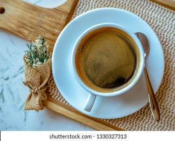black coffee in a coffee cup on wooden trays.