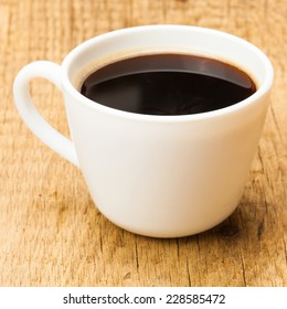 Black coffee in cup on wooden table