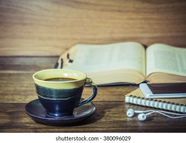 A black coffee cup on wooden background with smartphone over the small note book and burred of holy bible in background, vintage color