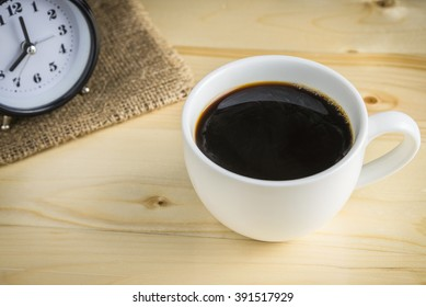 Black coffee in cup of coffee on wooden background