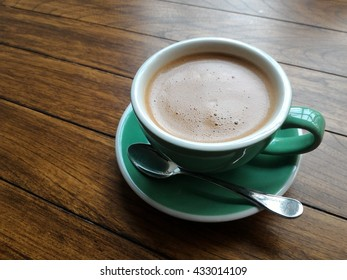 Black coffee in coffee cup on wooden table close up.