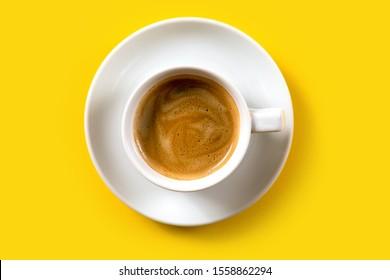 Café negro en una taza con fondo amarillo