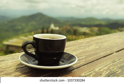 A black coffee cup rests on a table with mountain  background.