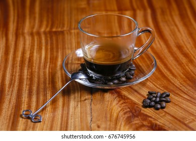 Black coffee cup and spoon on wooden table