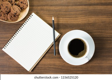 Black coffee in cup and white ceramic saucer Include oval wooden tray with chocolate chip cookies and notebook with pencil, Placed on the dark brown wood table.