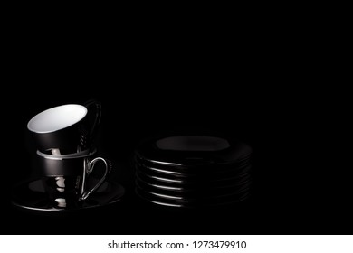 Black coffee. Dark abstract image of espresso cups and saucers. Silver and white coffee cups on black background with copy-space. Sophisticated rich dark roast represented in minimalist image.