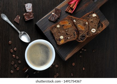 Black coffee and dark bread with nuts and dried fruits. On the surface of the table, pieces of dark chocolate and coffee beans are laid out. Dark background. View from above.
