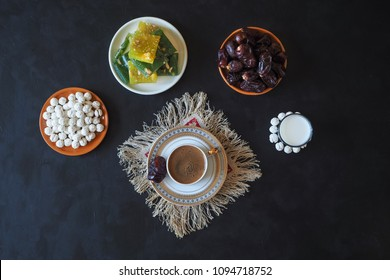 Black coffee and dates on the black table. Sweet food for Ramadan