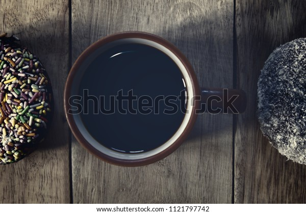 Black coffee and Donuts on wooden background, Coffee break, Free space for text, Top view.