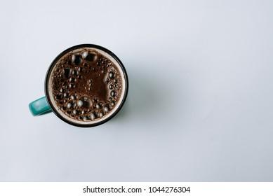 Black coffee in enamel mug. Top view.