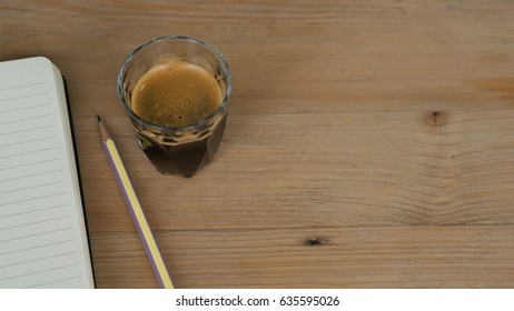 Black coffee / espresso shot in the on-the-rock glass put on the wooden beside by a pencil on the notebook which has line, brown color tone as vintage and classic, all on desk in the working space