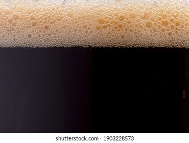 Black coffee with foam, close up photo.